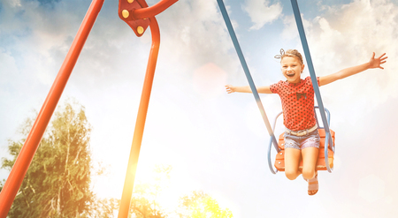 Little laughing girl swing on swing. Happy childchood concept image.