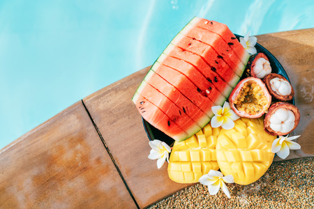 Still life image of tropical fruits and flowers near the pool: water melon, mango, mangosteen, passion fruit