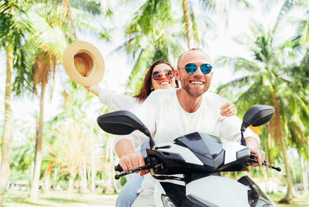 Laughing happy couple travelers riding motorbike during their tropical vacation under palm trees. Woman raised hand with hat up.