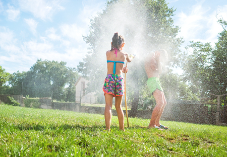 Sister and brother playing with watering hose in hot summer afternoon on 