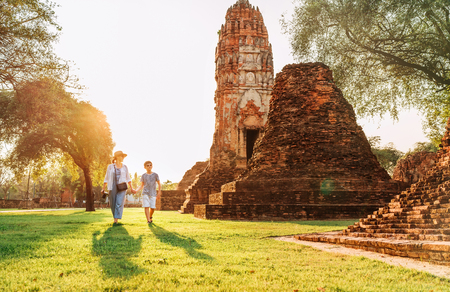 Mother and son tourists walking hand in hand in atcient Wat Chaiwatthanaram Buddhist temple ruines in holy city Ayutthaya, Thailand  in Auyttaya