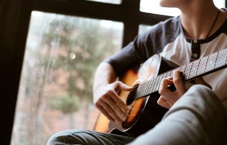 Man hands sitting on the big window windowsil and playing on guitar - fingers close up image 版權商用圖片