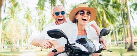 Smiling happy couple travelers riding motorbike during their tropical vacation under palm trees Stock Photo