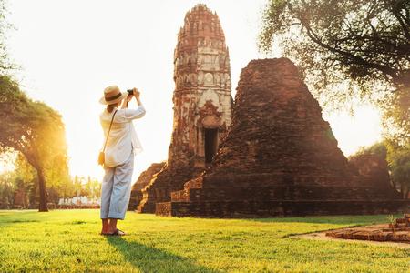 Woman traveler takes a photo of atcient Wat Chaiwatthanaram Buddhist temple in holy city Ayutthaya, Thailand 版權商用圖片