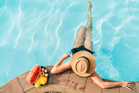 Top view of Woman in straw hat sitting on swimming pool side near plate of tropical fruits- camera