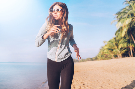 Fashionable young longhaired female have morning jogging on the seaside beach