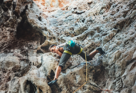Young mountain climber climbing on Climbing Route using rope on Tonsay beach in Krabi, Thailand. 版權商用圖片