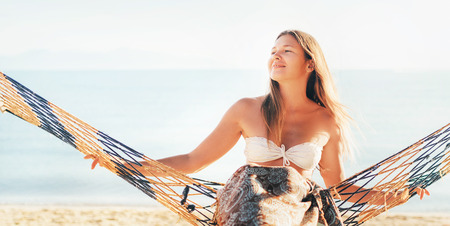 Happy smiling female swinging in hammock hinged between palm trees at the sea side