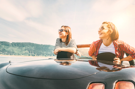 Two females friends traveling by cabriolet, have a stop brake to enjoy a mountain landsxapes