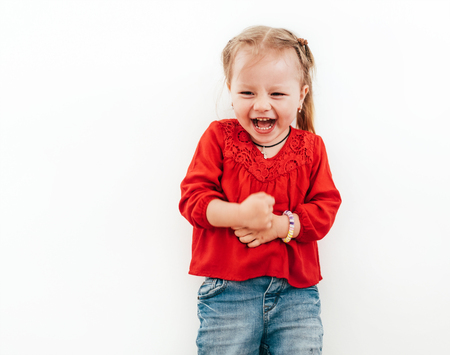 Happy emotions of Little girl dressed red blouse on the white background.