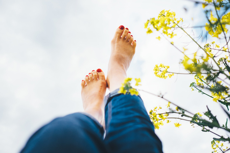 Happy female lying in deep yellow flowers meadow with bright sunny day optical sun beams flares. Happiness in nature concept Legs up POV image. 版權商用圖片