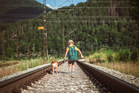 Little boy walking with big backpack and his beagle dog run on railway