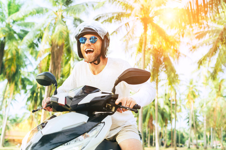 Happy smiling and screaming male tourist in helmet and sunglasses riding motorbike scooter during his tropical vacation under palm trees