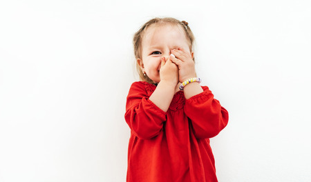 Confused emotions of Little girl dressed red blouse on the white background. Stock Photo