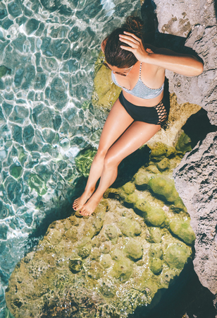Woman dressed in retro swim suit sun buthing in the sea lagoon. Healthy skin and safely sunbuthing concept