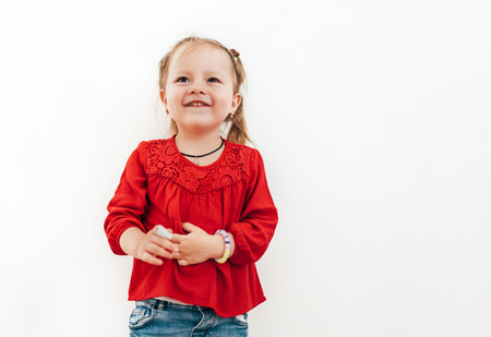 Happy smiling emotional little girl in red blouse on the white wall background 版權商用圖片
