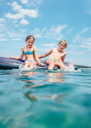 Little brother and sister  sitting  on inflatable mattress in the Adriatic sea. Happy summer holidays concept image.