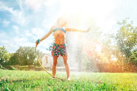 Cute little girl refresh herself from garden watering hose