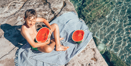 Summer plesuares: boy ready to eat big watermelon after swimming in the sea