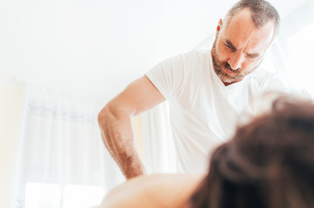 Bearded Masseur man doing massage manipulations on the low back area during young female body massaging. Health care concept image. Archivio Fotografico - 124333201
