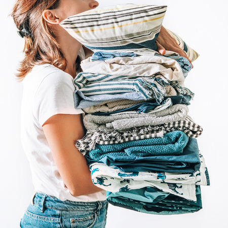 Woman takes in hands big pile blue and beige blankets, towels and other home textile 版權商用圖片