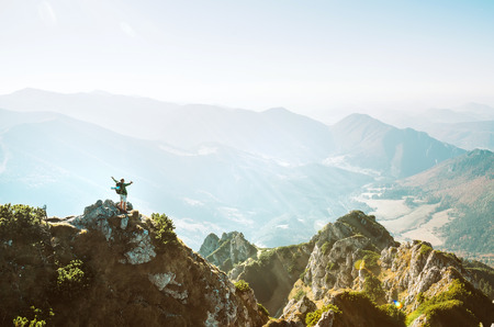 Mountain hiker with backpack tiny figurine stands on mountain peak with beautiful panorama 版權商用圖片