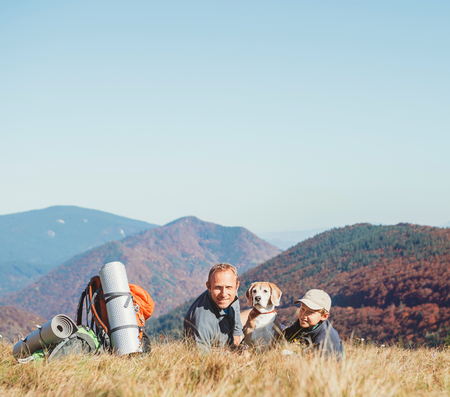 Father and son backpackers hikers rest on mountain hill with their beagle dog Stock Photo