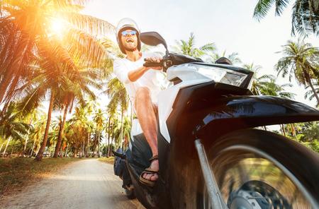 Man riding motorbike under palm trees