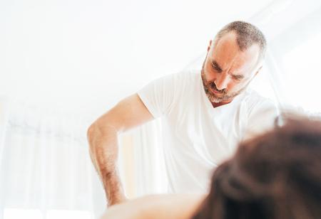 Homme masseur barbu faisant des manipulations de massage sur le bas du dos pendant le massage. Image de concept de soins de santé