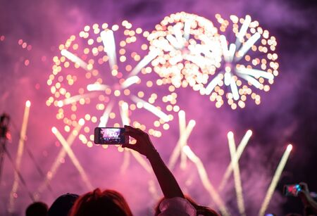 Raised hand with shooting horizontal night fireworks sky video smartphone