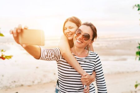 Two caucasian girlfriends hugging and posing for selfie on the sea side using smartphone.