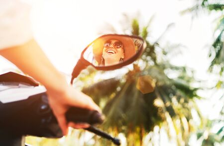 Smiling woman riding motorbike mirrored in rear view mirror with shining sunrays