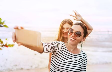 Two girlfriends posing for selfie on the sea side using smartphone Stock Photo