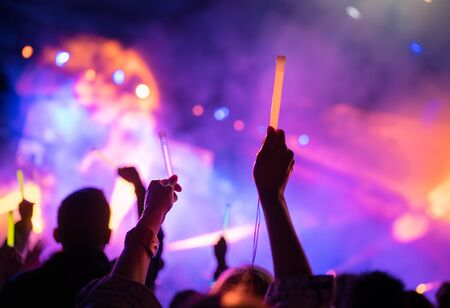 Young teenager girl fan raised up two hands with colored glowing sticks supporting favorite popular band on the night concert.