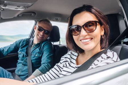 Cheerful young traditional couple has a long auto journey. Safety riding car concept wide angle inside car view image.