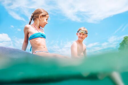 Sister and brother sitting on inflatable mattress and enjoying the sea water, have fun when swim in the sea.