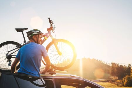 Man taking his bicycle from car roof. Mountain biking concept