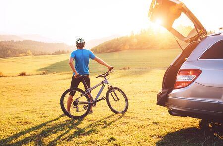 Man came by auto in mountains with his bicycle on the roof. Mountain biking concept