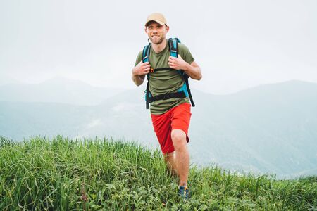 Uomo sorridente stanco dell'escursionista che cammina dal sentiero della catena montuosa del tempo nuvoloso nebbioso con lo zaino. Sport attivi backpacking concetto di stile di vita sano.