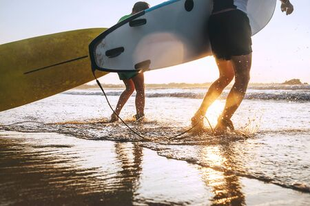 Son and father surfers run in ocean waves with surfing boards Stockfoto