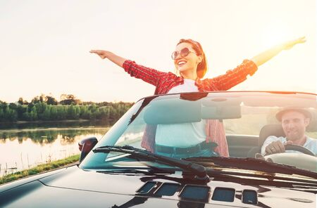 Happy couple in love go by cabriolet car in sunset time