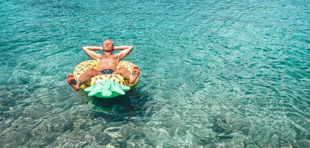 Man relaxing when swims on inflatable pineapple pool ring in crystal clear sea water. Careless vacation concept image.