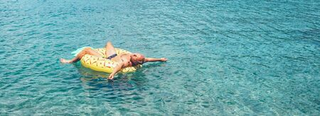 Man relaxing when swims on inflatable pineapple pool ring in crystal clear sea water.