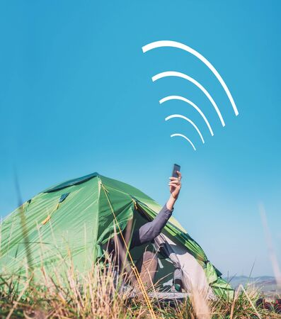 Traveler sits in touristic tent and try to catch cellular network