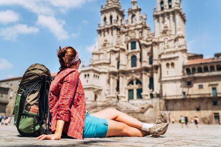 Las hembras jóvenes piligrim mochilero sentado en la plaza Obradeiro (plaza) en Santiago de Compostela