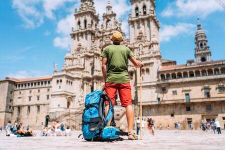 Joven mochilero peregrino de pie en la plaza Obradeiro (plaza) - la plaza principal de Santiago de Compostela como final de su peregrinaje del Camino de Santiago. Foto de archivo