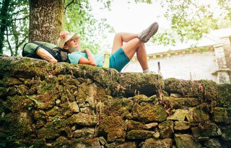 Peacefully Sleeping young female backpacker liying on the old stone castle fance and enjoying a rest time on the Way of Camino de Santiago