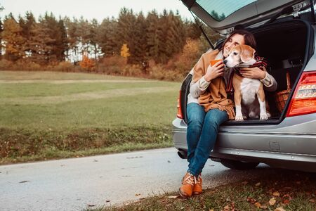 Woman with dog sit together in cat truck and warms цшер hot tea. Auto travel with pets concept image. Archivio Fotografico