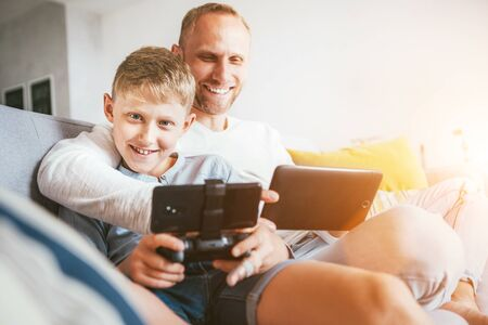 Father and son portrait with electronic devices playing. Sitting at home in cozy atmosphere Stockfoto - 132029448