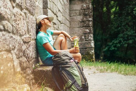 Very tired female backpacker resting on the bench near the old antique brick wall castle on the famous Camino de Santiago way. Stock Photo